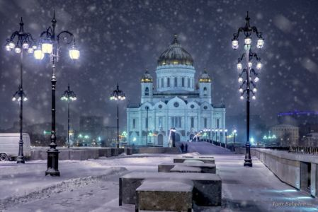 Snowfall on the background of the night view of the Cathedral of